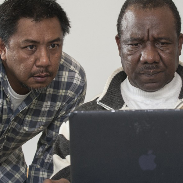 Photo showing a Carsey School student working on the computer while an instructor looks on.