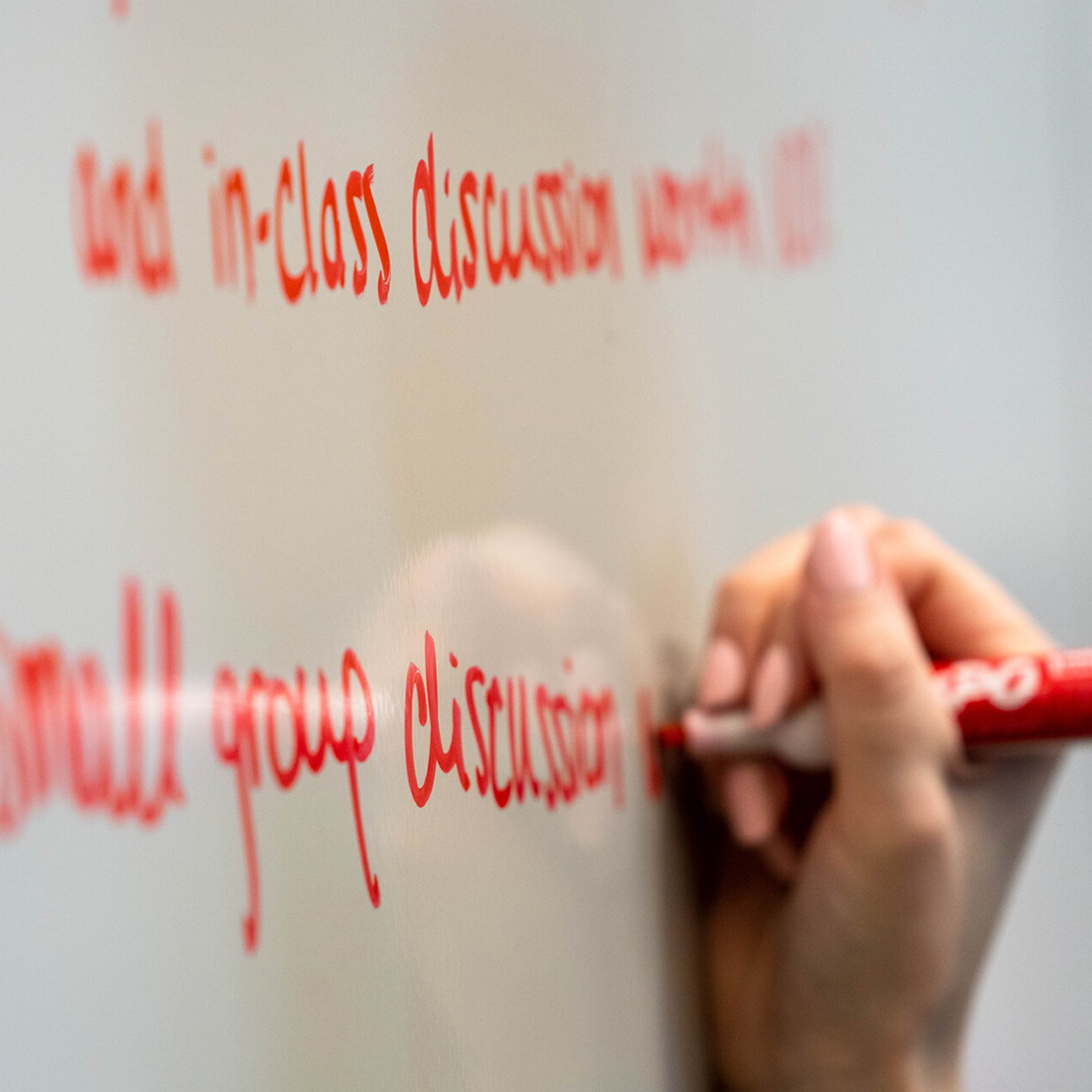 Image of a woman's hand writing red text on a white board.