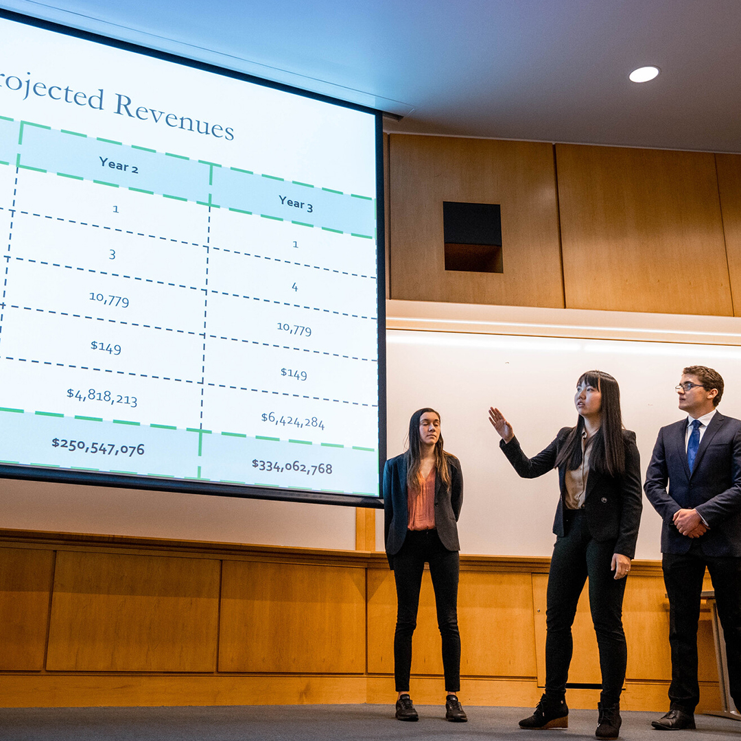 Three students standing in front of a screen with revenue information projected upon it
