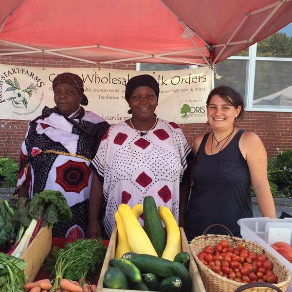 MCD graduate Charlene Higgins (far right) standing with vegetable vendors.