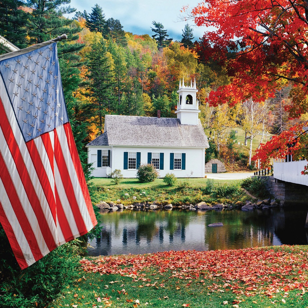 A photograph of a new hampshire church in the fall with an American flag hanging in the forefront