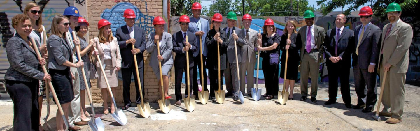 Image of team holding shovels and in hardhats
