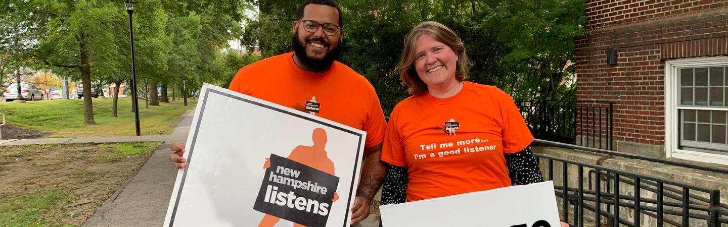 Carrie and Andres holding NH Listens signs in front of Huddleston Hall.