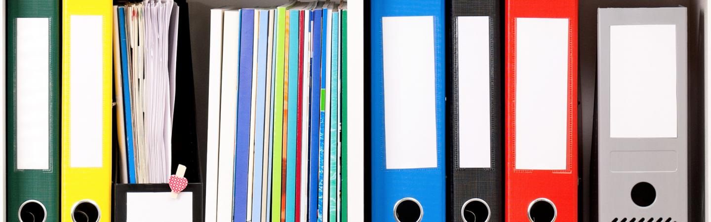 A photo showing multicolored binders and magazines organized on a shelf