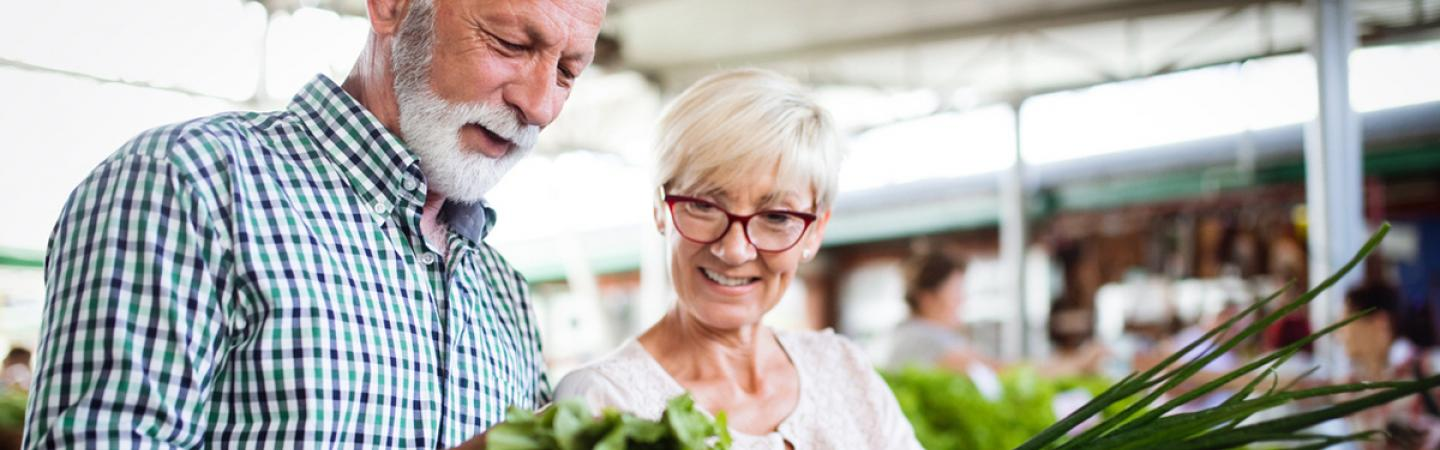 A mature couple looking at vegetables at a farmer's market