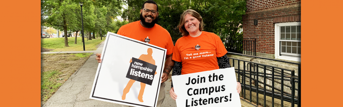 A photo of two NH Listens team members holding signs in front of Huddleston Hall at UNH Durham