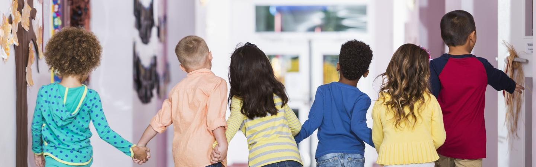 Image of Preschoolers Holding Hands and Walking Down School Hallway