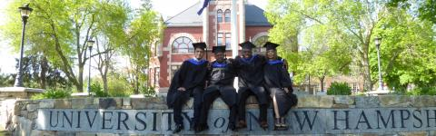 Recent graduates posing in front of Thompson Hall.