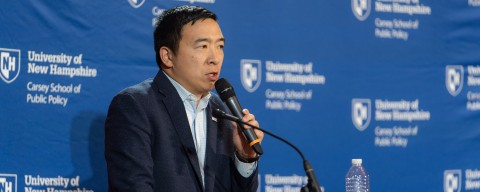 Andrew Yang speaking at a University of New Hampshire podium