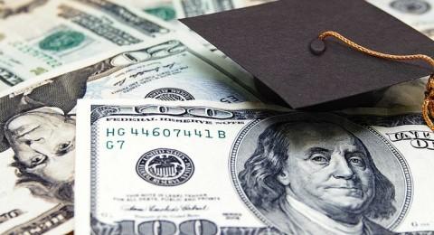 Photo of graduation cap on stacks of money.