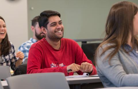 Two students sitting in a public policy classroom, listening to a lecture while smiling.