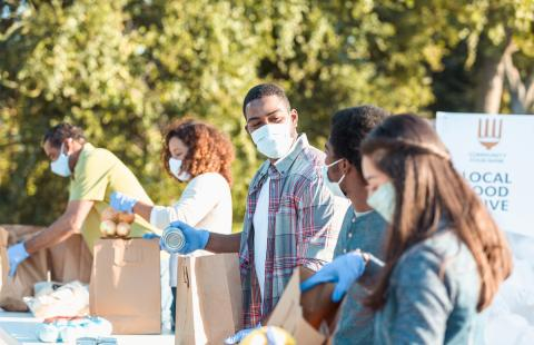 A group of nonprofit workers wearing masks and filling paper bags during a local food drive