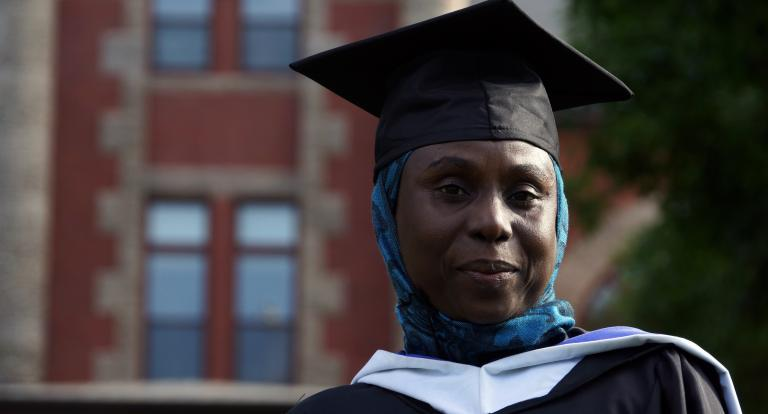 Safiya Adamu stands in her graduation cap in front of Carsey