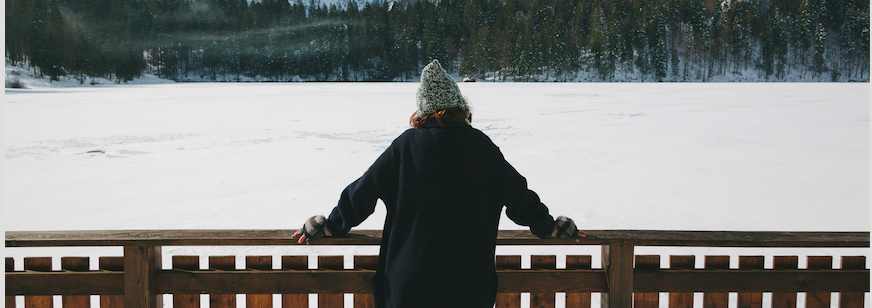 Image of a woman looking a snow covered lake