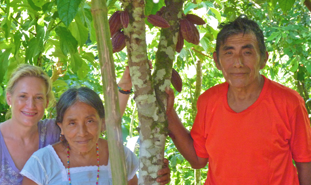 Robin with a man and a women standing among cacao trees.