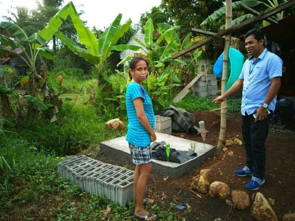 A man and a women standing near palm trees, next to a sewage treatment structure.