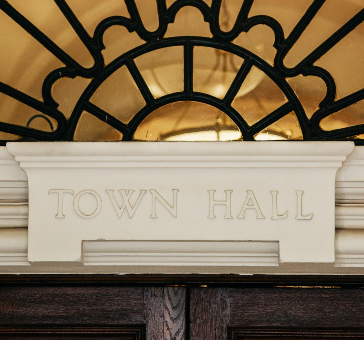 Photo of a town hall doorframe with the words Town Hall written on it.